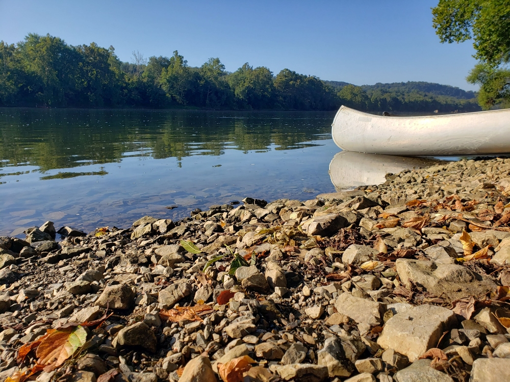 A canoe rests along the New River shoreline at the Whitethorne Boat Launch on a summer day.