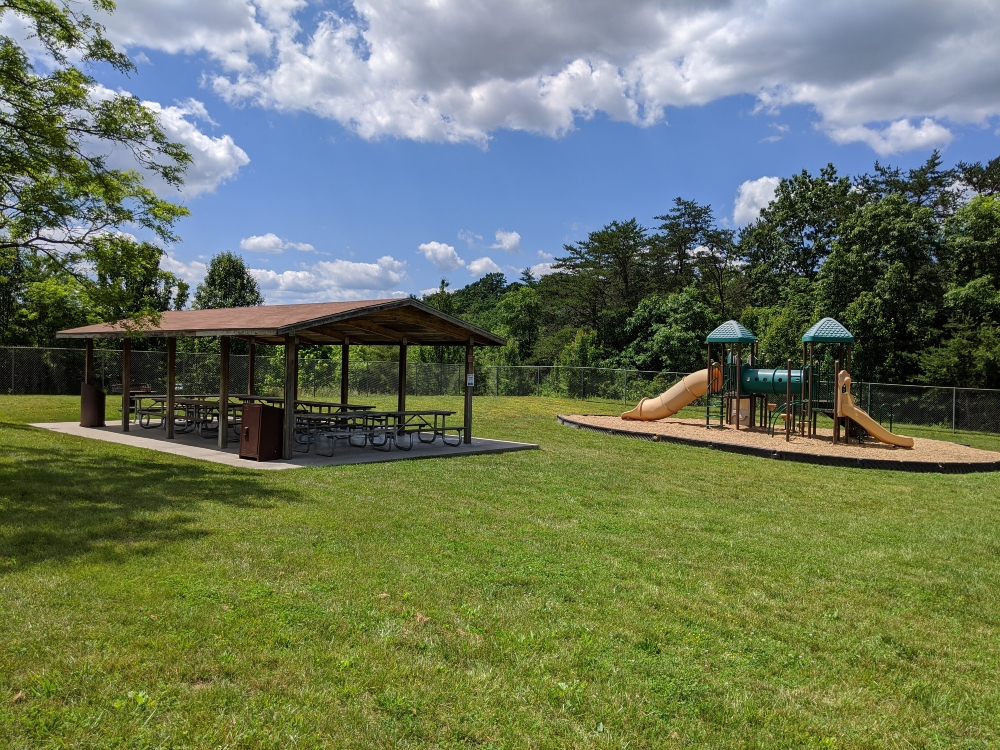 The playground and picnic shelter at Plum Creek Park are located next to each other and bordered by trees and green space on a sunny summer day.